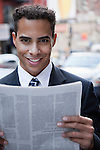 USA, New York, New York City, portrait of smiling businessman holding newspaper on street