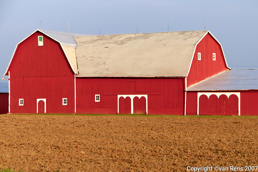Iconic red barn, red soil in morning on a crisp fall day.