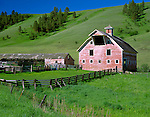 Wallowa County, OR  <br /> Weathered barn (dated 1915) with gambrel roof stands in a green valley of the Zumwalt prairie