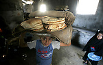 A Palestinians bake a bread in a traditional mud oven in Rafah refugee camp southern Gaza Strip on 20 June 2009. The PepsiCo Foundation and the United Nations World Food Programme (WFP) have announced a strategic partnership designed to enhance WFP's ability to deliver food and relief to the most vulnerable communities around the world.The foundation has committed $2.2 million for a program that convenes global logistics experts from PepsiCo to help strengthen WFP's response to growing hunger needs. PHOTO by Abed Rahim Khatib