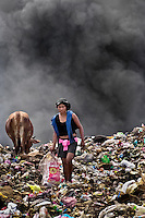 A Nicaraguan girl works on the burning pile of garbage in the garbage dump La Chureca, Managua, Nicaragua, 4 November 2004. La Chureca is the biggest garbage dump in Central America. Hundreds of trash recollectors search in tons of smouldering garbage mainly metals (copper, aluminium), others concentrate on glass which is cheap, but in bigger amount. The majority of the recyclers are families with children for whom recycling is a regular job. The children very often eat the food they find on the dump, none of them goes to school, they suffer from skin diseases, they have high levels of lead and DDT in blood.