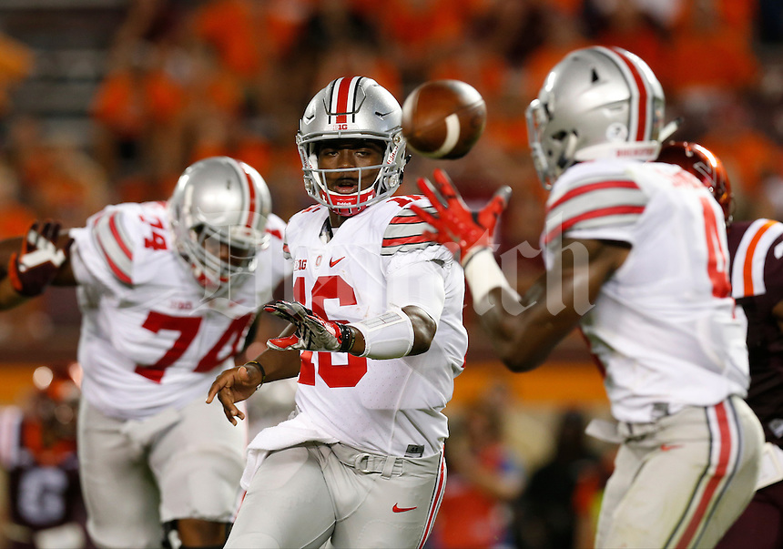 Ohio State Buckeyes quarterback J.T. Barrett (16) flips the ball to Ohio State Buckeyes running back Curtis Samuel (4) during Monday's NCAA Division I football game against the Virginia Tech Hokies in Blacksburg, Va., on September 7, 2015. Ohio State won the game 42-24. (Dispatch Photo by Barbara J. Perenic)