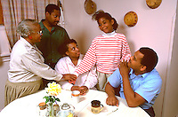 Extended African American family consoling 13 year old in the kitchen.  St Paul Minnesota USA