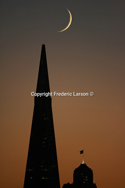 The setting crescent moon photographed from Treasure Island settled in between Nob Hills Mark Hopkins Hotel and Transamerican during the evening twilight in San Francisco, California.