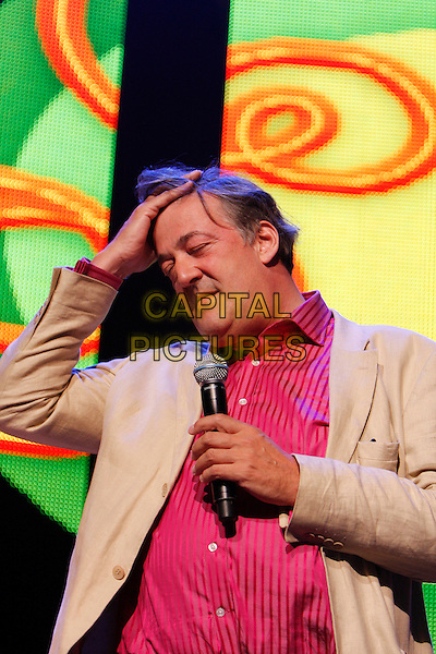 STEPHEN FRY.Performs as part of iTunes Festival 2010 at the Roundhouse, London, England, UK, July 18th 2010..half length red shirt beige jacket on stage live stand-up show concert gig microphone  yellow hand touching hair head funny .CAP/MAR.© Martin Harris/Capital Pictures.