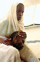 Sudan. West Darfur. Habilah. The non-governmental organization (ngo) Médecins sans Frontières (MSF) Switzerland runs a medical program. A woman with a veil on the head holds in arms her sick husband who suffers from a high blood pressure. They both wait for a medical consultation. © 2004 Didier Ruef