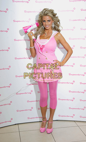 JORDAN - KATIE PRICE .Launches Jordan Haircare Electricals at Superdrug, Kensington High Street, London, England..October 25th 2007.full length pink dress top hairdryer leggings shoes hand on hip.CAP/ROS.©Steve Ross/Capital Pictures