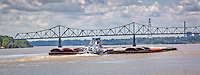 A large barge traveling down the Mississippi River at the Helena West-Helena River Park in Helena Arkansas.<br /> The U.S. Route 49 Bridge that connects Helena-West Helena, AR with Lula, Mississippi.