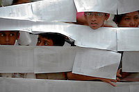 People peer through voters' lists as votes are counted at the polling station in central Yangon April 1, 2012. Pro-democracy leader Aung San Suu Kyi won a seat in parliament on Sunday, her party said, after a historic by-election that is testing Myanmar's nascent reform credentials and could convince the West to end sanctions. REUTERS/Damir Sagolj (MYANMAR)