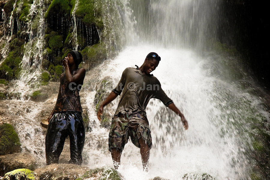 Haitian men perform a bathing and cleaning ritual under the waterfall during the annual religious pilgrimage in Saut d'Eau, Haiti, July 16, 2008. Every year in summer thousands of pilgrims from all over Haiti make the religious journey to the Saut d'Eau waterfall (100km north of Port-au-Prince). It is believed that 150 years ago the spirit of Virgin Mary (Our Lady of Mount Carmel) has appeared on a palm tree close to the waterfall. This place became a main pilgrimage site in Haiti since then. Haitians wearing only underwear perform a bathing and cleaning ritual under the 100-foot-high waterfall. Voodoo followers (many Haitians practise both voodoo and catholicism) hope that Erzulie Dantor, the Voodoo spirit of water, manifest itself and they get possessed for a short moment, touched by her presence.