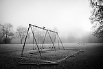 An empty swingset in an open foggy field.