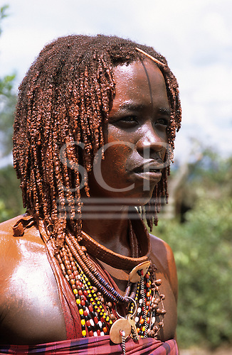 Lolgorian, Kenya. Siria Maasai Manyatta; a moran, red ochre coloured braided hair, shell and bead decorations, keys.