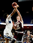 UNCASSVILLE, CT-031818JS14- Sacred Heart's Zachary Francisco (33) gets his arm hit by Notre Dame-Fairfield's Noreaga Davis (20) while putting up a shot during their Division I championship game Sunday at Mohegan Sun Arena. No foul was called on the play. <br /> Jim Shannon Republican-American