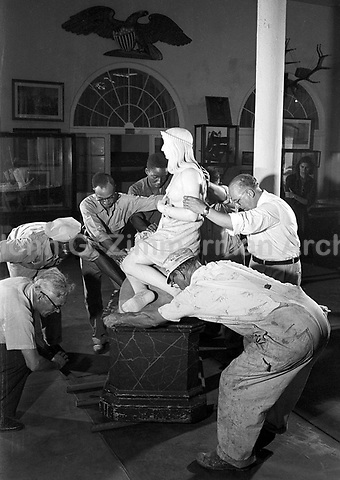 Museum staff installs sculpture in gallery, Presbytere, New Orleans Louisiana, 1953. Credit: © John G. Zimmerman Archive