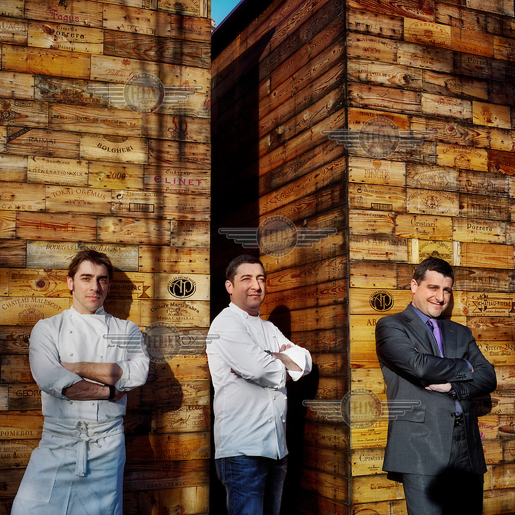 The Roca brothers (Jordi, the dessert chef, left; Joan, the main chef, centre; and Josep, the sommelier and maitre d', right) stand in front of stacked used wine boxes. Together they run El Celler de Can Roca restaurant in Girona.