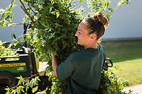 """NWA Democrat-Gazette/CHARLIE KAIJO Horticulturalist Honey Sue Miller of the Bentonville Parks and Rec carries leaves, Saturday, June 9, 2018 along SE """"J"""" Street in Bentonville. <br /> <br /> The Bentonville Parks Conservancy pruned the trees along SE """"J"""" street, between SE 8th Street and HWY 102 Saturday as part of tree maintenance days that it will hold throughout the summer to help develop tree canopies throughout the city's parks and trails. <br /> <br /> The Bentonville Parks Conservancy is a non-profit organization that works with the city to help develop and maintain the city tree canopy and parks. Part of their vision is to develop a volunteer work force that will meet throughout the year to work on tree maintenance as needed by the city and parks department.<br /> <br /> 14 volunteers showed up Saturday to help prune about 100 trees."""