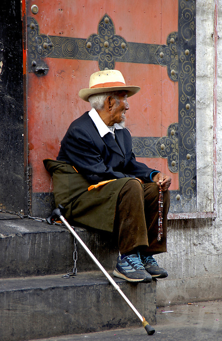Waiting for the day to go by, an old man sitting at a trditional house entrance with his prayer beads. Lhasa, Tibet
