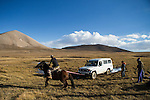 Snow Leopard (Panthera uncia) conservationist, Zair Kubanychbekov, and ranger, Temirlan Baktygul, on horseback trying to get car unstuck, Sarychat-Ertash Strict Nature Reserve, Tien Shan Mountains, eastern Kyrgyzstan