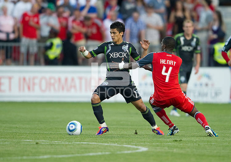 Seattle Sounders FC forward Fredy Montero #17 and Toronto FC defender Doneil Henry #4 in action during an MLS game between the Seattle Sounders FC and the Toronto FC at BMO Field in Toronto on June 18, 2011..The Seattle Sounders FC won 1-0.