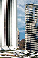 The Agua & Aon Buildings &and the top of the Pritzker Pavillion sit against a cloud studded sky in Chicago, Illlinois