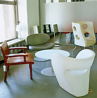 A collection of chairs, including a white Victoria & Albert Chair by Ron Arad, surround a round table in the cafe of the Design Museum in Milan