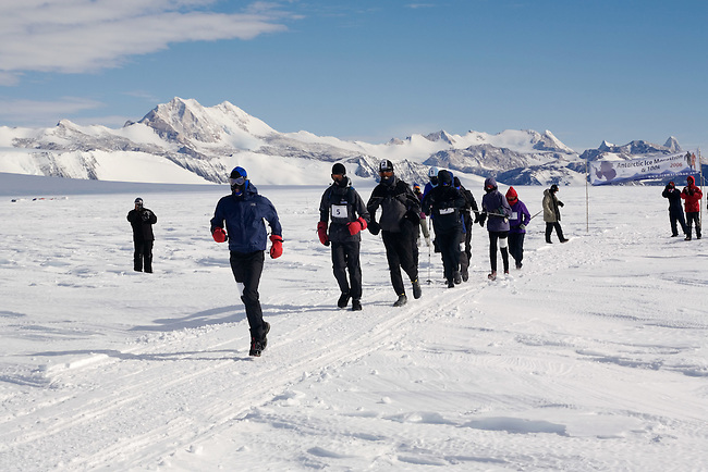 The Runners competing in the 2006 Antarctic Ice Marathon pass the Start banner. Patriot Hills. Antarctica.
