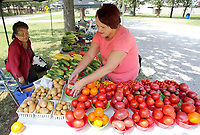 NWA Democrat-Gazette/DAVID GOTTSCHALK   Moua Lee, with Lee Farm, watches as Christie Smith, of Gentry, Tuesday, August 8, 2017, selects tomatoes and squash at Gentry's Farmer's Market at City Park. The market is open on Tuesday and Thursday from 8:00 a.m. to 5:00 p.m..