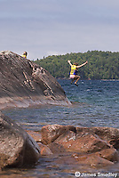 Young girls in life jackets jumping and swimming off rocky bluff at a lake