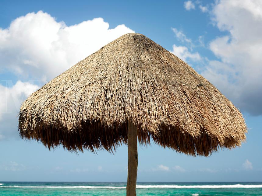 Mexico Quintana Roo Yucatan Peninsula Akumal Mayan Riviera,palapa against a cloudy blue sky and the sea