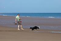 Holkham, Norfolk, England, 03/08/2009..Man walking a border collie dog on Holkham beach.