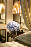 An arrangement of blue hydrangea flowers and a lit lamp stand on a bedside table.