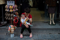 A woman shopkeeper plays with a toddler in Qianmen Street area of Beijing on June 1, 2012. Qianmen Street area has a history of more than 570 years. The shopping area was called Zhengyangmen Street during the Ming and Qing Dynasties, and finally named Qianmen Street in 1965. (Leica M9, 50mm f2)