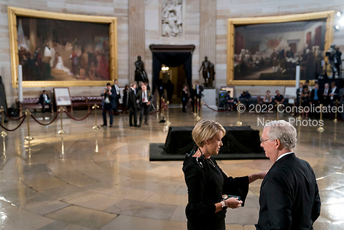 Senate Majority Leader Mitch McConnell of Ky., right, speaks to an aide before the casket of Sen. John McCain, R-Ariz., lies in state in the Rotunda of the U.S. Capitol, Friday, Aug. 31, 2018, in Washington. (AP Photo/Andrew Harnik, Pool)