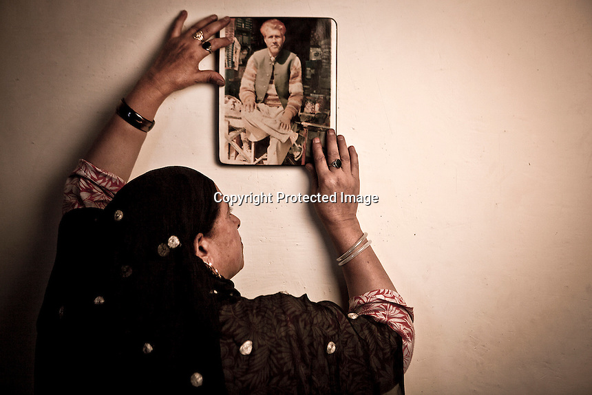 Misra shows Abdul Rasheed's portrait. She is 50-years-old woman. Her expressionless face is silent, quite. Misra was rendered half widow on 2nd July 1995, when the Indian army entered into her family house and took away her husband Abdul, in front even of their little son's eyes. During years she was looking for her loved one, from one military base to another, one jail to another, but he is truly disappeared. Srinagar, Indian administrated Kashmir.