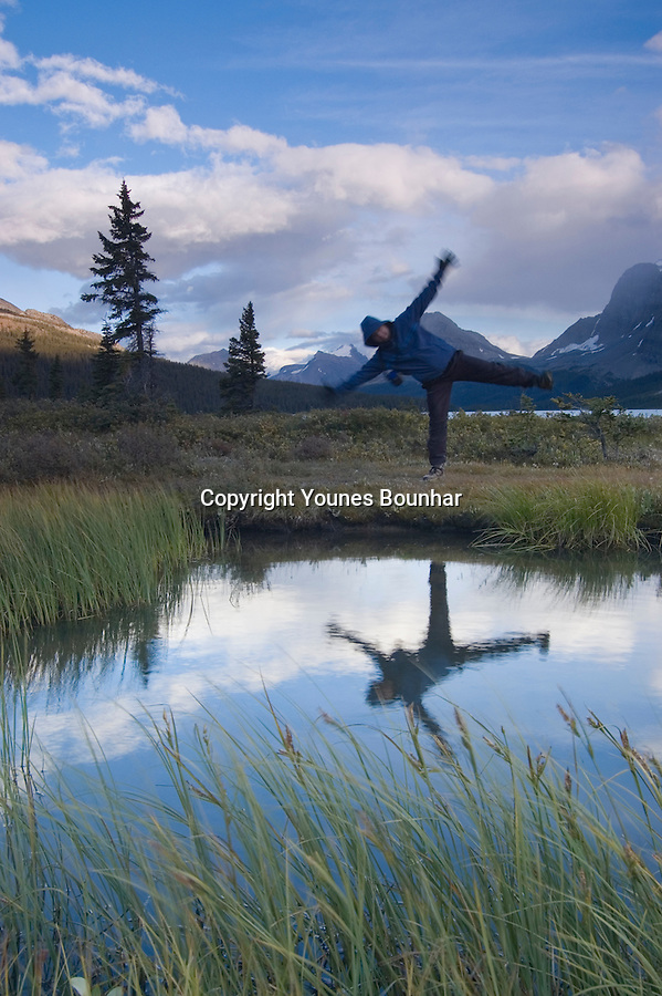 Playful man, balancing act, reflecting in pond by Bow Lake with Crowfoot glacier in the background