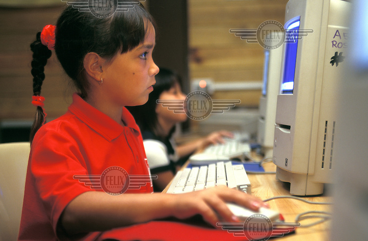 Eight year old Alexis Abala, who is half Aboriginal, uses a computer in an IT lesson at Ross Park school..
