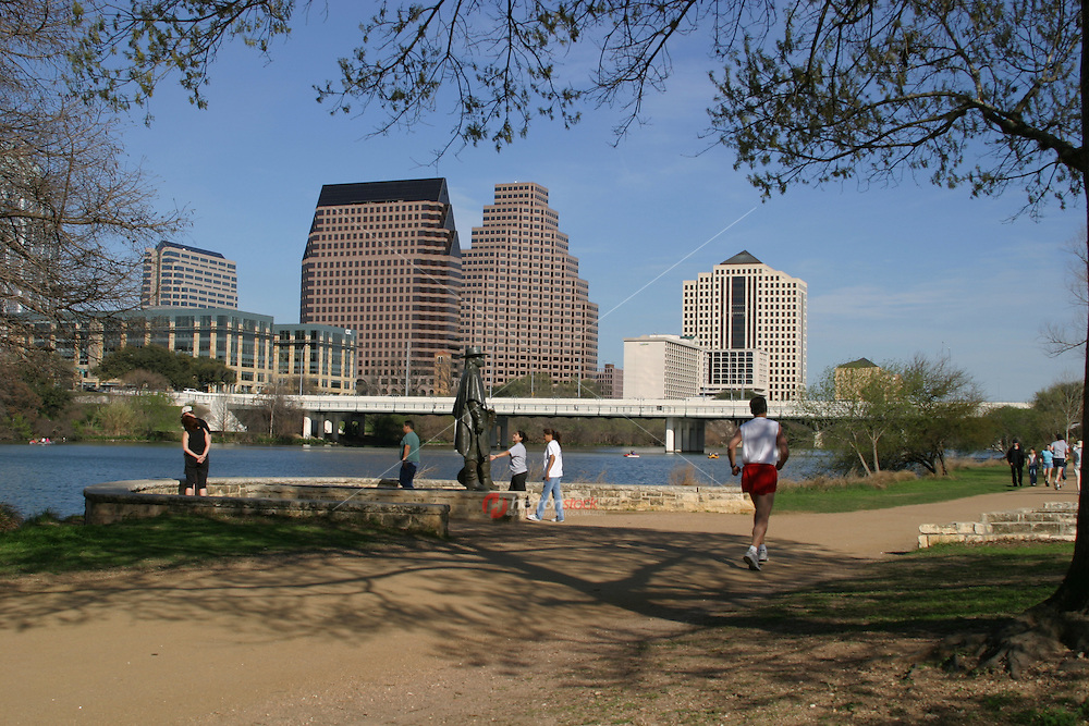 Runners and tourist visit the SRV Stevie Ray Vaughn Memorial Statue at Auditorium Shores.