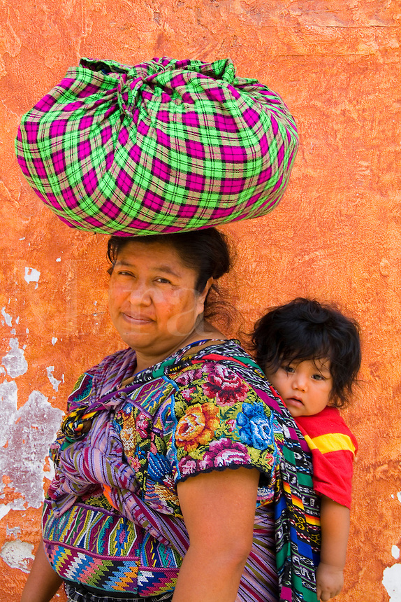 Local colorful woman against bright wall with local print dress carrying her baby on back in tourist village of Antigua Guatemal
