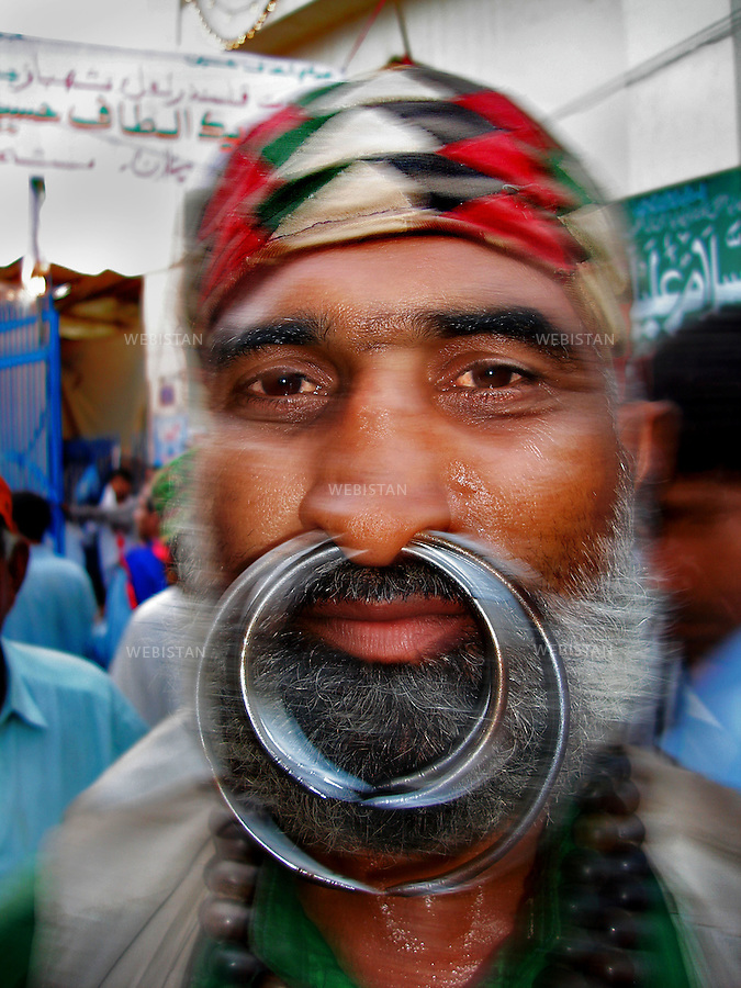 SEHWAN SHARIF, PAKISTAN - SEPTEMBER, 2006:  Portrait of a dervish with strange piercings and rings in his nose during the annual celebration of the Urs of Lal shahbaz Qalandar, a 13th century Sufi Master worshiped alike by Hindus and Muslims. Born as Seyed Shah Hussain (Usman) Marandi, he later on titled as Lal (red) Shahbaz ( Falcon) Qalandar (as he belonged to Qalandria order of sufism).