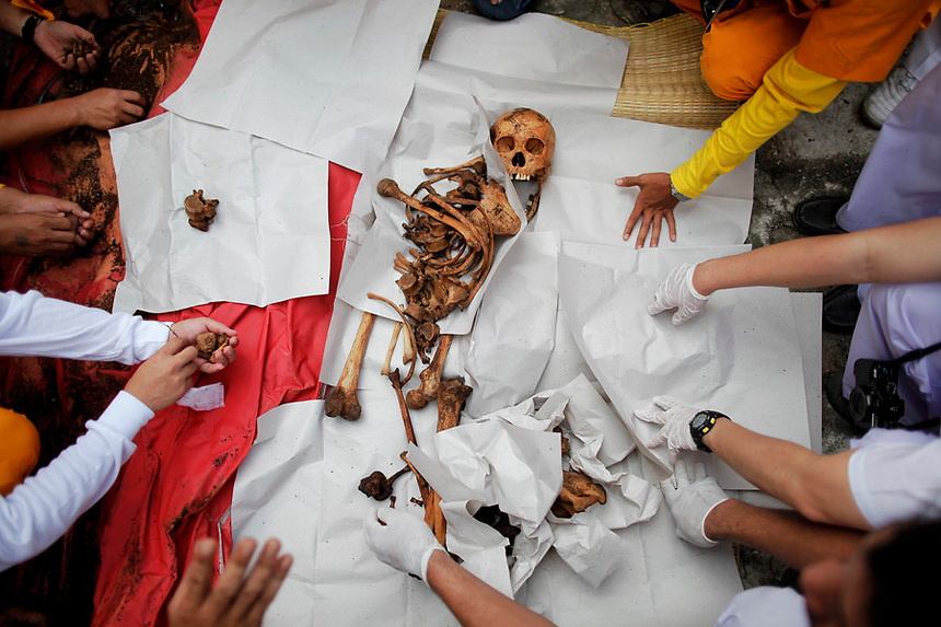 People take unclaimed human remains out of a grave during a Thai Chinese ceremony at the Mang Teung Sua Jung Cemetery in Chonburi province southeast of Bangkok March 18, 2012. Every 10 years, hundreds of people wearing white, a customary colour for funerals and visiting temples, gather at this cemetery to exhume and cremate corpses as they believe they are helping the dead who have no friends or relatives. The ashes of the unclaimed bodies are spread on the sea to make room at the burial ground for more unclaimed bodies in the coming years. The tradition originated 90 years ago after diseases like Malaria killed many of Thais of Chinese descent living in Chonburi.  REUTERS/Damir Sagolj (THAILAND)