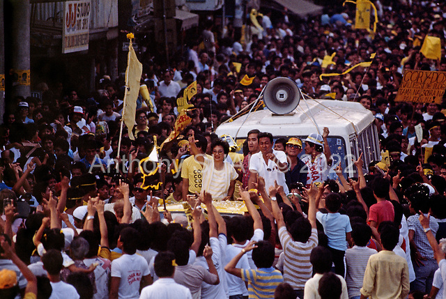 "Manila, Philippines<br /> February 1986<br /> <br /> Corazon Aquino campaigning for President of the Philippines in 1986.<br /> <br /> Corazon Aquino was born into one of the wealthiest families in the Philippines, Mrs. Aquino began her political education by playing the dutiful wife as the political career of her husband, Benigno Aquino Jr., expanded. In less than 20 years he emerged as one of the chief potential rivals of Mr. Marcos, who was then president. When Mr. Marcos declared martial law in 1972, her husband was arrested and imprisoned for seven years. He was assassinated in 1983 after returning to the Philippines from a three-year exile in the United States. Mr. Marcos was widely blamed for the murder. It was at Mr. Aquino's funeral that Mrs. Aquino, became a national symbol, demonstrating the dignity and composure that would characterize her most difficult moments as president. <br /> <br /> Mrs. Aquino came to power through what amounted to popular acclaim -- what the Philippino people called ""people power"" -- expressed by huge crowds that gathered in support of her. Her popularity reached its peak during her presidential campaign against Mr. Marcos in January 1986, when she was surrounded by enthusiastic crowds chanting, ""Cory! Cory! Cory!'""<br /> <br /> Her act of knocking down a dictator and bringing democracy to the Philippines was a high point in the country's modern history, and it offered a model for nonviolent uprisings that has been repeated often in other countries.<br /> <br /> Mrs. Aquino, was often criticized as an indecisive and ineffectual leader. But she combined passivity and stubbornness and an unexpected shrewdness to hold firm against powerful opponents from both the right and the left, and one of her greatest accomplishments as president was fending off a half dozen coup attempts. <br /> <br /> The restoration of democracy, and the transition to a new president, were Mrs. Aquino's prime legacies. Yet she led demonstrations against all 3 of her successors.<br /> <br /> She died on July 31, 2009."