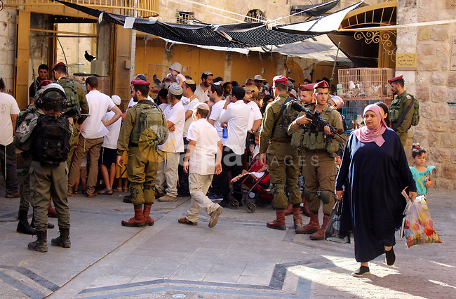 Israeli soldiers stand guard as Jewish settlers tour of the streets in the Old City of the West Bank city of Hebron, on August 24, 2019. Photo by Mosab Shawer