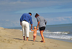 parents walking with toddler on beach