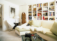 A feminine sitting room is furnished with an L-shaped banquette sofa with built-in shelves along one wall