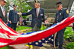 Removing American Flag to reveal monument made with steel from World Trade Center, at the Merrick Post #1282 American Legion Tenth Annivesary of 9/11 event are (left to right) Rabbi Paul Kirchner, Father Eric Fasano, Adjutant Robert Tom Riordan PCC,; and North Merrick Fire Dept. Ex. Chief Henry Hinrichs, at Merrick Veterans Memorial Park, Merrick, New York, USA, on September 11, 2011.