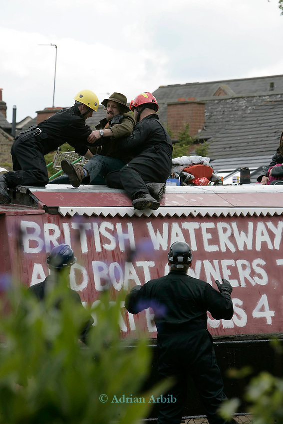 in an operation involving around 100 police and baliffs a boater (Ceri Fielding)  is grappled off the roof of his boat by British Waterways baliffs at the Castlemill Boatyard, Oxford.  Narrowboaters are  requesting an alternative site to replace the 160 year old boatyard in the heart of  the city.  British Waterways are selling the site for housing and have not provided an alternative site. 8 boats  are craned out on the wharf in protest and BW are  forcibly craning them back in to the water today.  BW are also threatening to impound boats