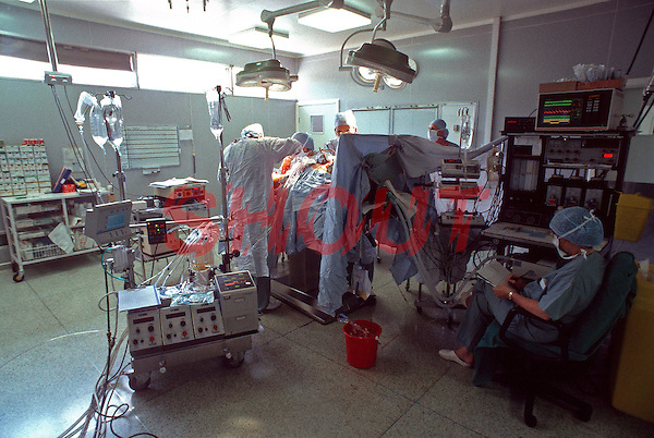 Surgeons performing heart transplant surgery in a hospital operating theatre. In the foreground can be seen the perfusion technologist who operates the heart lung machine used for cardiopulmonary bypass during surgery. This image may only be used to portray the subject in a positive manner..©shoutpictures.com..john@shoutpictures.com
