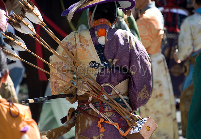 """A participant dressed in traditional attire carries his arrows on his back as he heads toward the start of the """"yabusame-shinji"""" mounted archery ritual on the 3-day Reitaisai grand festival in Kamakura, Japan on  16 Sept. 2012.  In the Azumakagami -- a book of Japanese history covering 87 years from 1180 to 1266 in the Kamakura Era, a hunt and mounted archery event was held on August 15 1187 and it is this in which the shrine's Reitaisai has its roots. For over 800 years since the history and tradition of the event have been continued at the shrine. Photographer: Robert Gilhooly"""