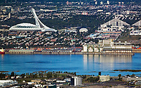 aerial photograph of Olympic Park, Montreal, Quebec, Canada viewed from Longueuil across the Saint Lawrence river. One of the twin Olympic Village structures is at right.