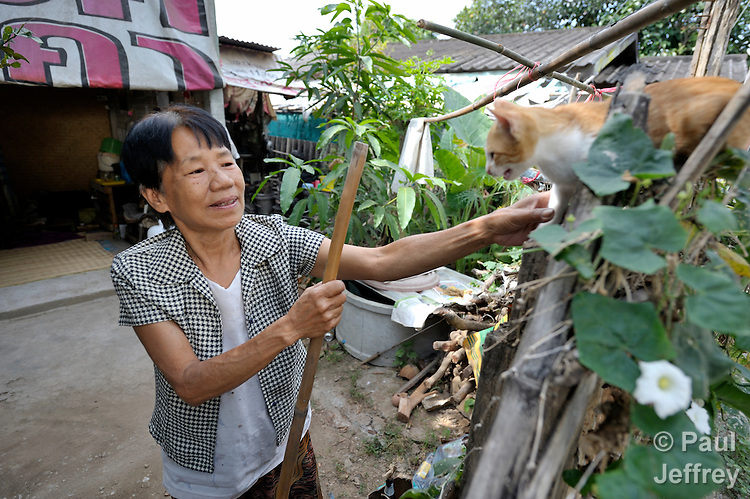 Pranom Kantawong, a woman living with HIV, visits with her cat outside her home in the city of Chiang Mai, Thailand.